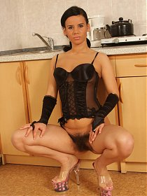Winnie takes us to the kitchen and does a striptease to show her hairy pussy on webcam